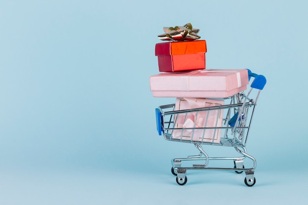 Gifts stacked in shopping card on blue surface