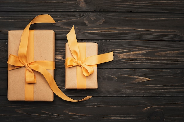 Gifts tied with golden ribbon on wooden background and copy space