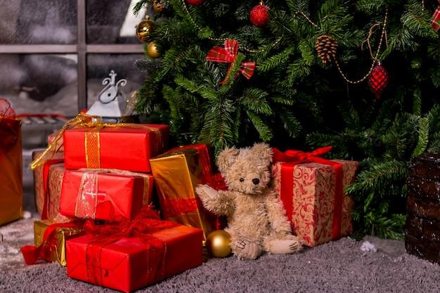 クリスマスツリー、おもちゃのクマとボックス、居心地の良い家の新年の概念の下のギフト。サンタを待っている、クリスマスの赤いギフトボックス。テディベアとプレゼントはクリスマスツリーの下に配置。