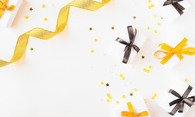 Gifts with bright ribbons and confetti on a light background