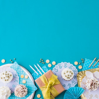 Gifts with muffins on plate and tray at the edge of blue background