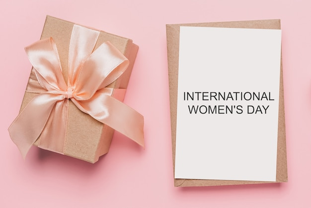 Gifts with note letter on isolated pink background, love and valentine concept with text international womens day