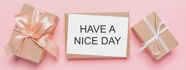 孤立したピンクの背景にメモ文字、テキスト付きの愛とバレンタインのコンセプトのギフトhave a nice day