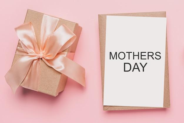 孤立したピンクの背景にメモの手紙、テキストの母の日と愛とバレンタインのコンセプトのギフト