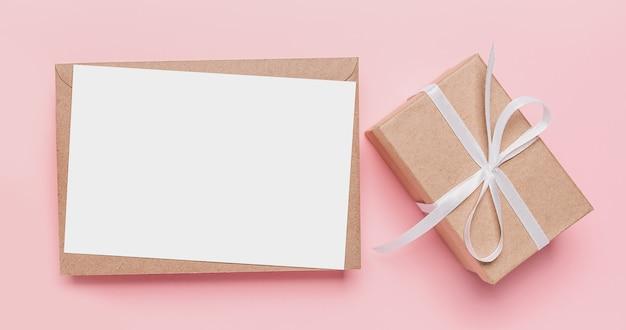 孤立したピンクの背景、愛とバレンタインのコンセプトにメモの手紙とギフト