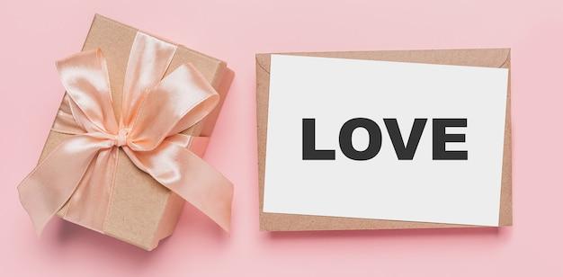 격리된 분홍색 표면에 메모 문자가 있는 선물, 텍스트 사랑이 있는 사랑과 발렌타인 개념