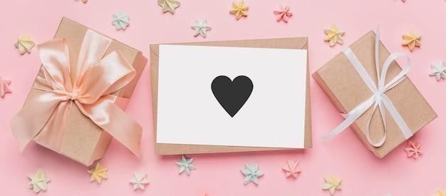과자, 사랑, 발렌타인 컨셉이 있는 격리된 분홍색 표면에 메모가 있는 선물