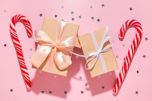 Подарки с красными рождественскими конфетами и звездами конфетти льются на пастельный розовый фон, вид сверху. плоская планировка. праздник нового года, концепция атмосферы праздника