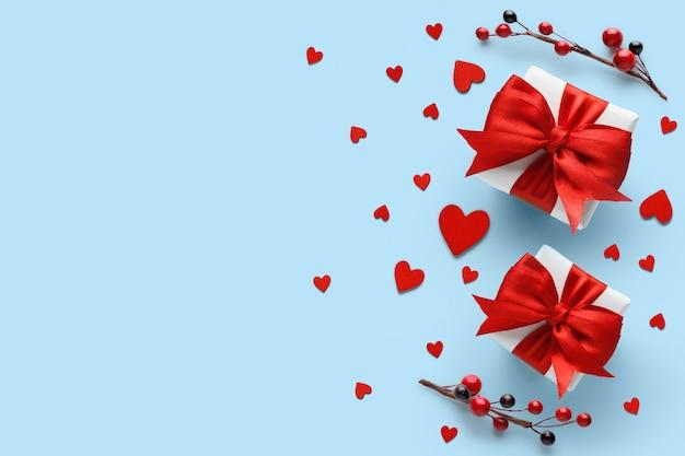 Подарки с красным атласным бантом и сердечками. плоская планировка, вид сверху, копия пространства