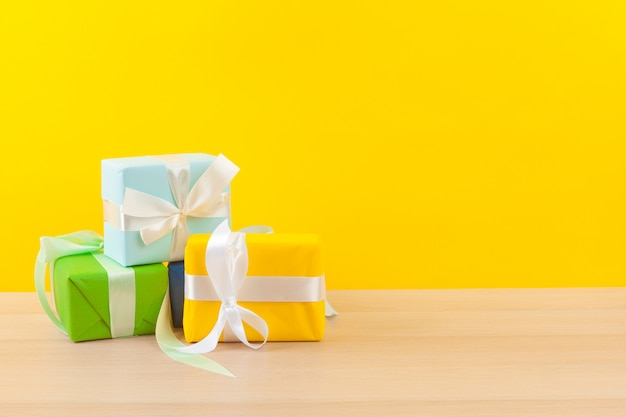 Gifts with ribbons on bright yellow