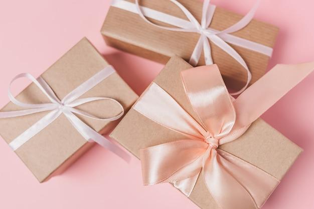 孤立したピンクの背景、愛とバレンタインのコンセプトにwihteリボンのギフト