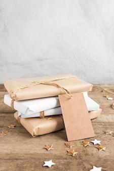 Подарки, завернутые в бумагу, на деревянном столе с золотыми блестками и большой биркой для места для копии.