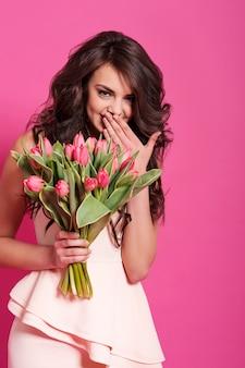 新鮮な花で美しい女性をくすくす笑う