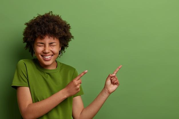 낄낄 거리는 짙은 피부색의 여성은 오른쪽 상단 모서리에 손가락을 가리키고, 긍정적 인 것을 웃으며, 녹색 옷을 입은 하얀 이빨을 보여 주며, 멋진 제안이 진실한 감정을 표현함을 암시합니다.