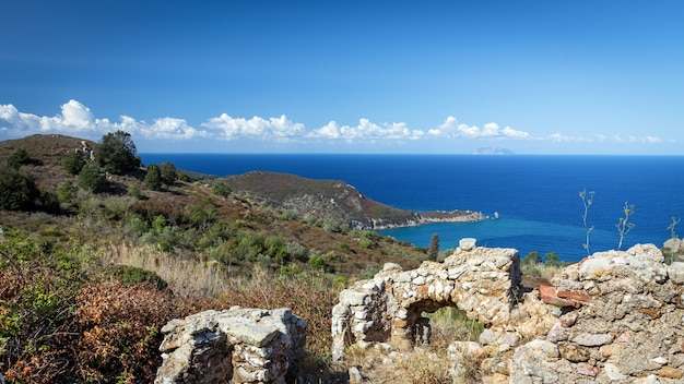 Остров джильо со средневековыми руинами на переднем плане и морской бухтой со спокойным синим средиземным морем.