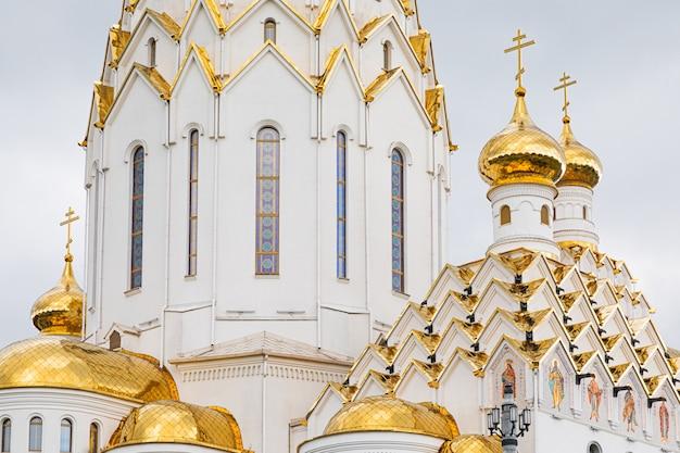 Золоченые купола христианской церкви с витражами Premium Фотографии