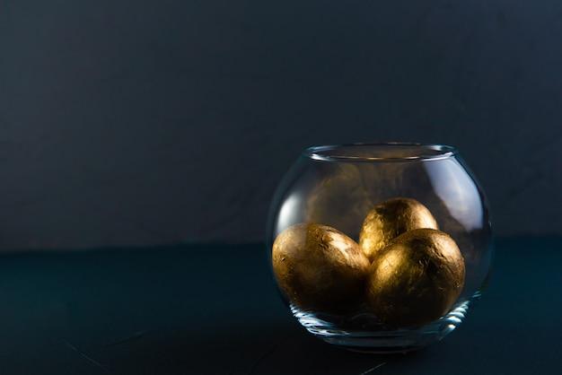Золоченые пасхальные яйца в прозрачной вазе на бетонном фоне в классическом синем цвете