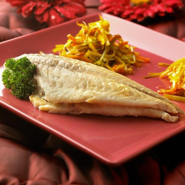 ガーネット皿に野菜の付け合わせを添えて調理したヨーロッパヘダイ