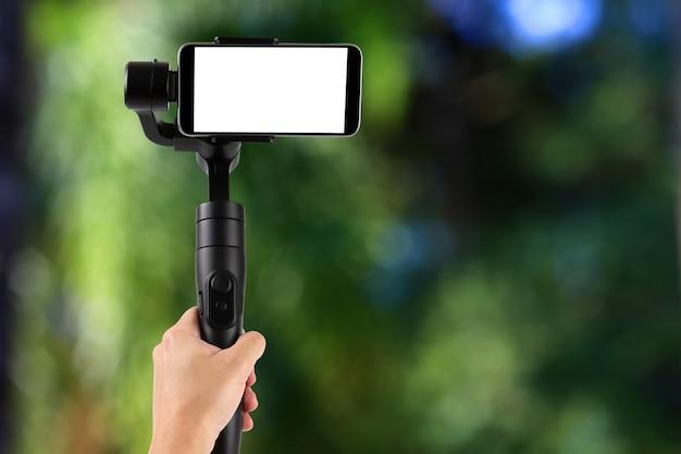 ジンバル。携帯電話にスタビライザーを使用し、森を撮影する青年。セレクティブフォーカス