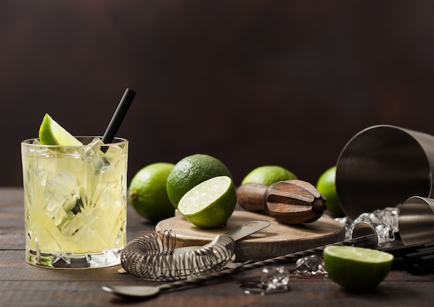 Gimlet kamikaze cocktail in crystal glass with lime slice and ice on wooden surface with fresh limes and strainer with shaker.