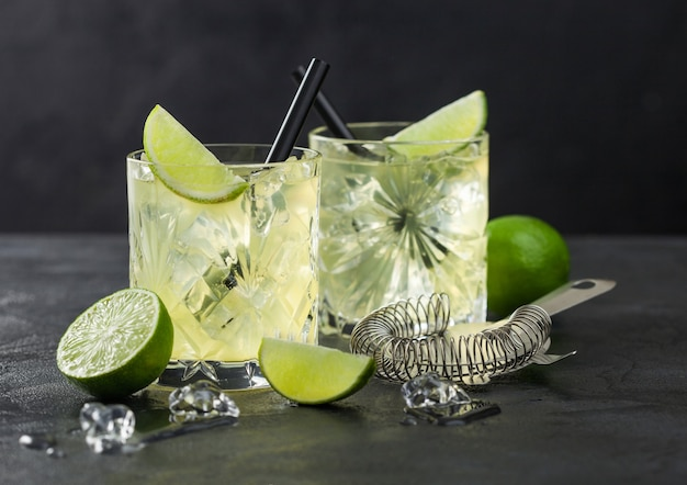 Gimlet kamikaze cocktail in crystal glasses with lime slice and ice on black surface with fresh limes and strainer.