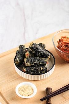 김마리, 유리 국수 또는 잡채로 속을 채운 김(김) 롤로 만든 한국식 튀긴 스낵 튀김. 일반적으로 떡볶이와 함께 반찬으로 제공됩니다. 하얀 접시에 젓가락과 김치가 곁들여져 나온다