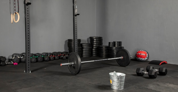 Gimnasio con barra y discos masequipo de crossfit para hacer ejercicio