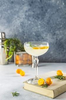 Джин-тонический коктейль с кумкватом фортунелла в бокале шампанского на светло-серой поверхности стола