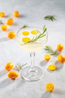 Джин-тонический коктейль с кумкватом фортунелла в бокале шампанского
