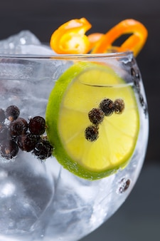 Gin tonic cocktail macro closeup with juniper berries