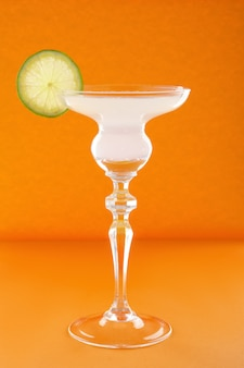 Gin tonic cocktail on orange wall