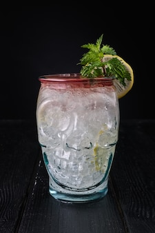 Gin and tonic cocktail with cherry syrup in skull cup