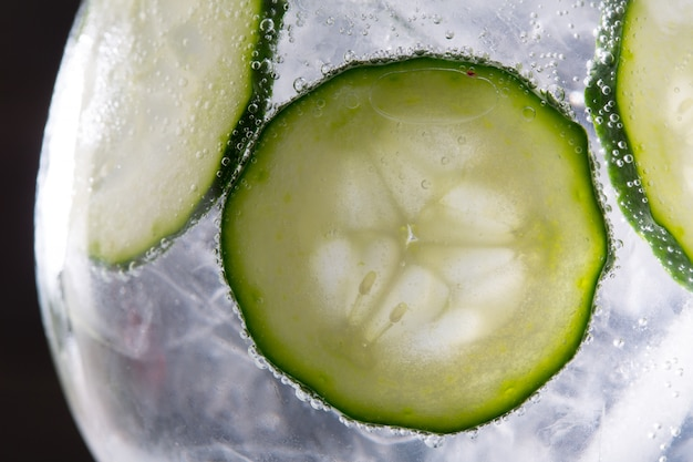 Gin tonic cocktail with cucumber and ice  macro closeup