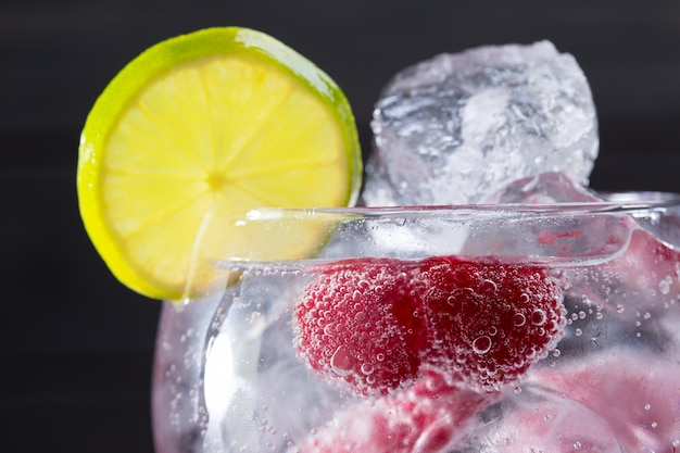 Gin tonic cocktail with raspberry and ice macro closeup