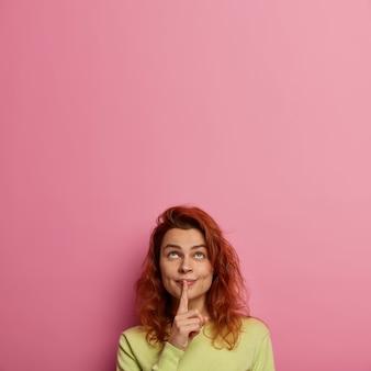 Рыжая взрослая женщина прижимает указательный палец к губам, готовит сюрприз, никому не просит, хочет молчать, носит зеленый джемпер, смотрит вверх