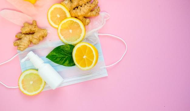 ピンクのテーブルに医療マスクと生姜とレモン