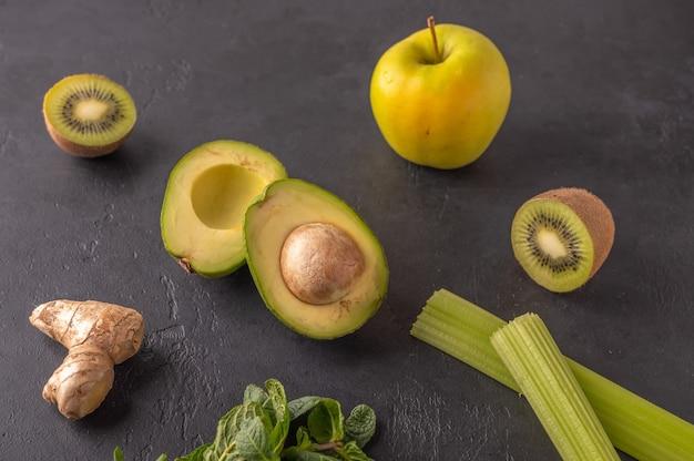 暗い背景にジンジャー、アボカド、リンゴ、キウイ、セロリ。スムージーの材料