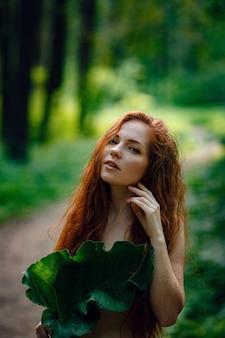 森の中で服を着ていない彼女の胸に大きな休暇を保持している生姜の美しい女性