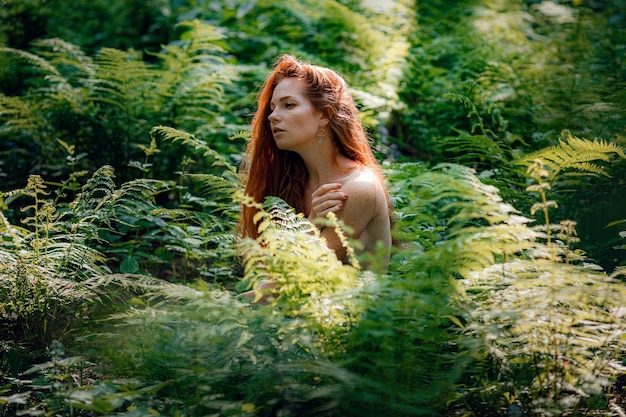 美しい日光の森で茂みの後ろでポーズをとって服を着ていない生姜美しい女性