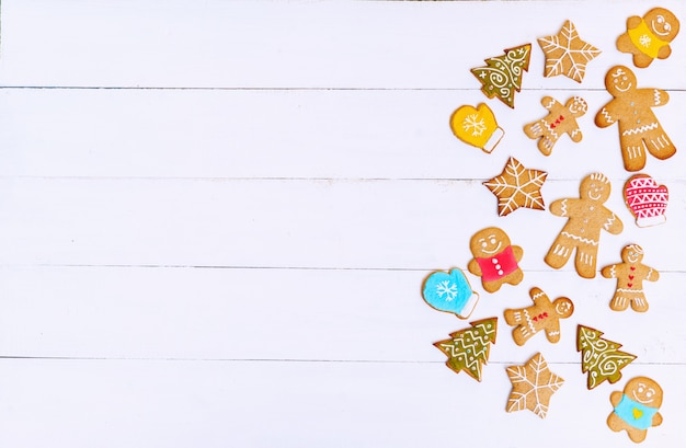 Ginger biscuits in the shape of men, stars and trees on sackcloth and white wooden surface. christmas concept