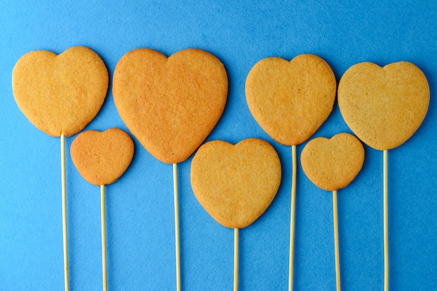 Ginger biscuits on a stick in the form of hearts on a blue background