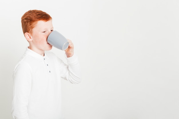 Ginger boy drinking from mug