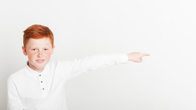 Ginger boy pointing to copyspace