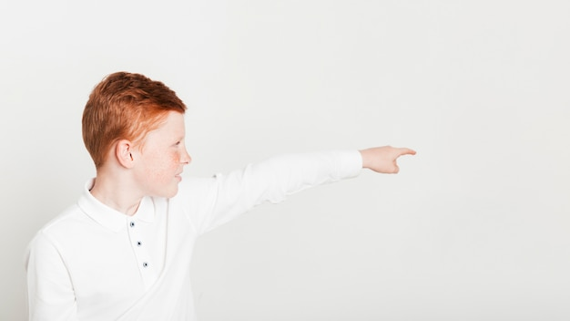 Ginger boy pointing towards copyspace