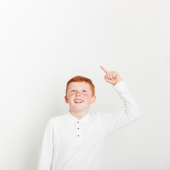 Ginger boy pointing up towards copyspace