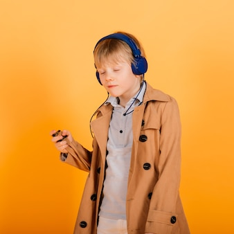 Ginger boy in shirt adjusting headphones while listening to music after school studies against yellow background
