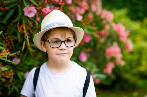 Ginger boy in the straw hat and big glasses near the green bush with pink flowers in the summer park