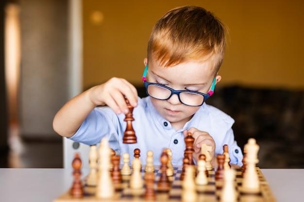 Рыжий мальчик с синдромом дауна в больших очках играет в шахматы дома