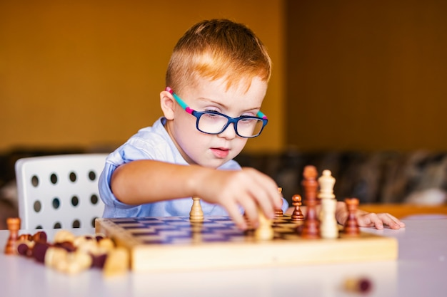 Ginger boy with down syndrome with big glasses playing chess at home