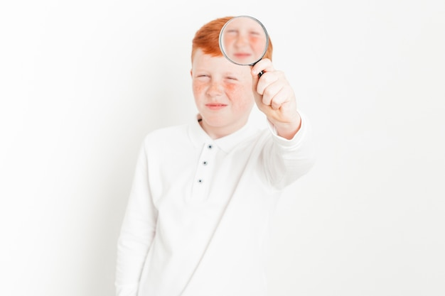 Ginger boy with magnifying glass